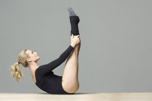 Blond woman doing stretching exercises on the floor - VGF00220