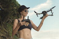 Indonesia, Bali, Nusa Dua, woman holding drone at the beach - KNTF02707