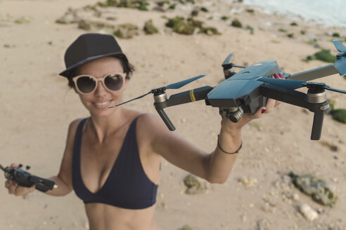 Indonesia, Bali, Nusa Dua, woman holding drone at the beach - KNTF02710