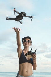 Indonesia, Bali, Nusa Dua, woman flying drone at the beach - KNTF02713