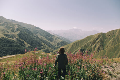 Rear view of woman looking at mountains while standing amidst plants against clear sky during sunny day - CAVF61612