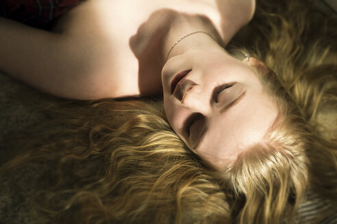 High angle view of woman with blond hair sleeping on bed at home - CAVF61621