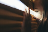 Close-up of cute smiling girl looking through window blinds at home - CAVF61630