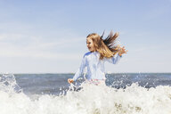Cheerful girl jumping in sea on shore against sky during sunny day - CAVF61633