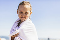 Portrait of smiling girl wrapped in towel standing at beach against sky during sunny day - CAVF61636