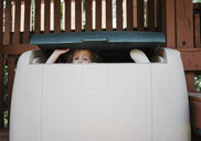 Portrait of cute girl hiding in box at playground - CAVF61717