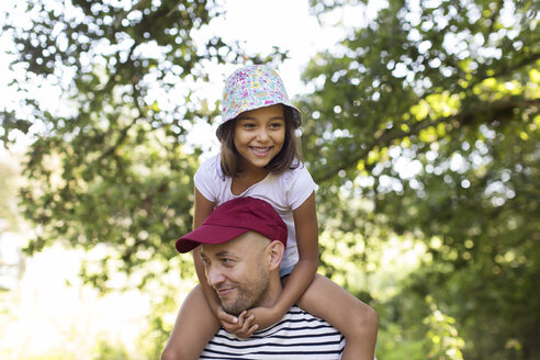 Father carrying daughter on shoulders in park - CAIF22808