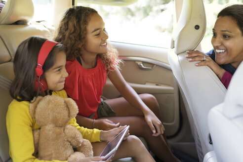 Mother and daughters riding in car - CAIF22817