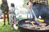 Man barbecuing hamburgers, kebabs and corn cobs - CAIF22847