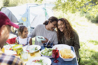 Affectionate, happy family enjoying lunch at campsite table - CAIF22859