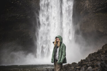 Smiling female hiker in rain jacket at waterfall, Whistler, British Columbia, Canada - CAIF22871