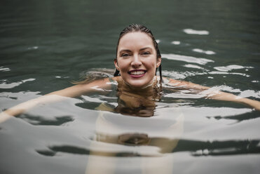 Portrait smiling young woman swimming in lake - CAIF22886