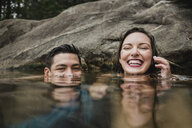 Portrait playful young couple swimming in lake - CAIF22889