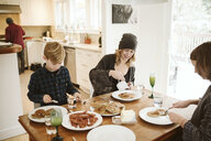 Family eating breakfast at kitchen table - CAIF22892