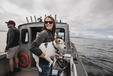 Portrait smiling woman with dog on fishing boat - CAIF22895