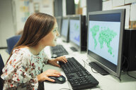 Curious junior high school girl student looking at map on computer in classroom - CAIF22910