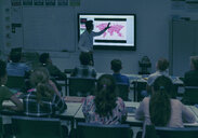 Students watching geography teacher at projection screen in dark classroom - CAIF22928