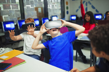 Junior high school boy students using virtual reality simulators in classroom - CAIF22940