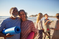 Portrait happy senior couple with yoga mats on sunny beach during yoga retreat - CAIF22955