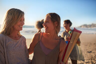 Happy mother and daughter with yoga mat on sunny beach during yoga retreat - CAIF22961