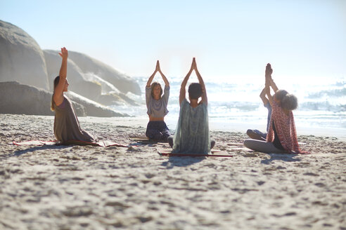 Serene people in circle meditating on sunny beach during yoga retreat - CAIF22964