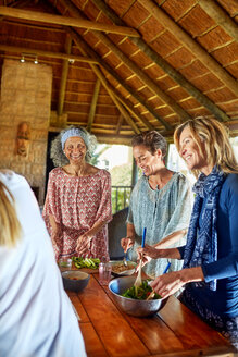 Women preparing healthy meal in hut during yoga retreat - CAIF22970