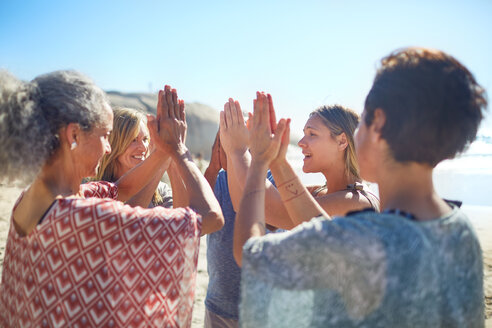 Group standing in circle with hands clasped on sunny beach during yoga retreat - CAIF23027