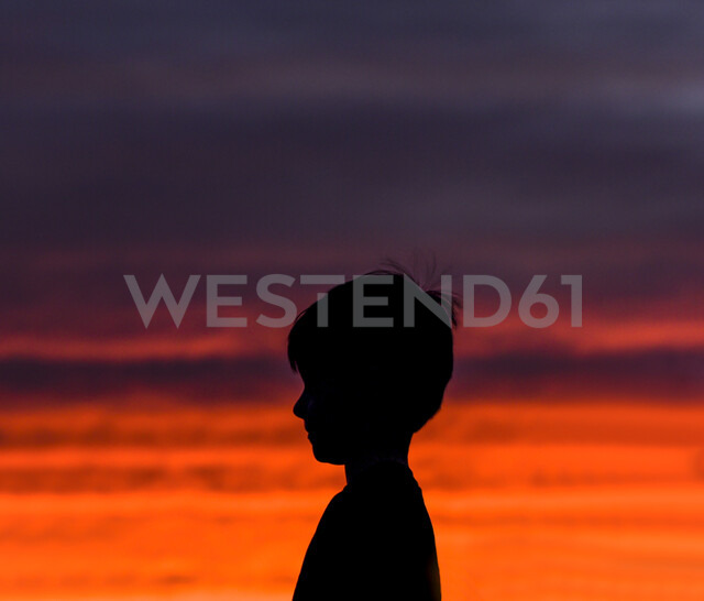 Side view of silhouette boy standing against dramatic sky in sunset - CAVF61745 - Cavan Images/Westend61