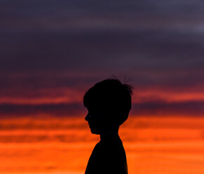 Side view of silhouette boy standing against dramatic sky in sunset - CAVF61745