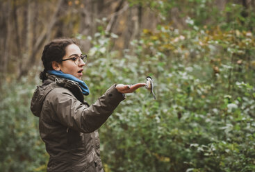 Excited girl feeding white breasted nuthatch in forest - CAVF61757