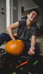 Boy removing seeds from pumpkin while sitting on floor at home - CAVF61766