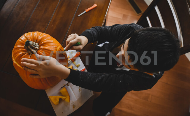 High angle view of boy making Jack O' Lantern at home during Halloween - CAVF61769 - Cavan Images/Westend61