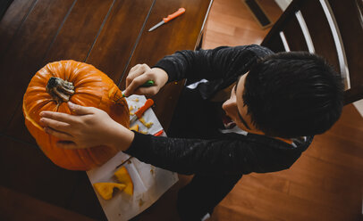 High angle view of boy making Jack O' Lantern at home during Halloween - CAVF61769