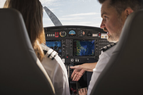 Rear view of male pilot showing dashboard to female trainee in airplane at airport - CAVF61799