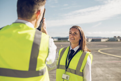 Rear view of male engineer showing airplane parts to female trainee while standing against blue sky on airport runway - CAVF61802
