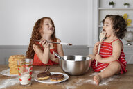 Cute sisters eating chocolate while sitting at wooden table against wall - CAVF61814