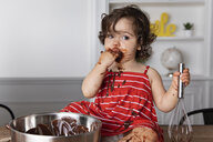 Messy baby girl eating chocolate while sitting on table against wall at home - CAVF61820