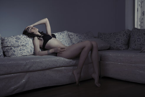 Young woman in black lingerie lying on sofa at shaded room - AZF00136