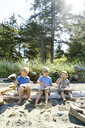 Brothers eating food while sitting on log at beach during sunny day - CAVF61838