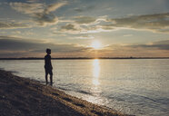 Silhouette boy standing at shore against sky during sunset - CAVF61844