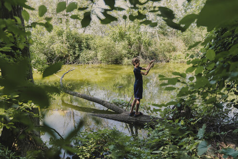 Full length of boy with fishing rod standing on fallen tree in lake at forest - CAVF61847