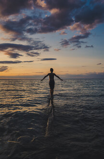 Rear view of carefree boy with arms outstretched walking in sea against sky during sunset - CAVF61856