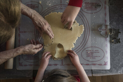 Cropped hands of grandchildren and grandmother cutting dough with pastry cutters on table at home - CAVF61904
