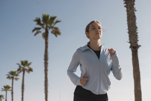Confident woman jogging against palm trees and sky during sunny day - CAVF61916