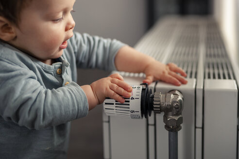 Baby boy playing with thermostat of heater - SEBF00021