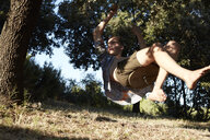 France, teenage boy on a swing at tree - AMEF00008