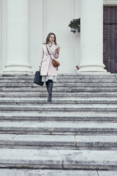 Austria, Vienna, young businesswoman walking downstairs looking at cell phone - ZEDF01924