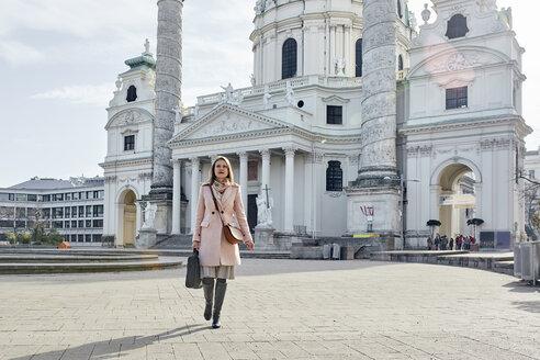 Austria, Vienna, young businesswoman with laptop bag crossing Karlsplatz - ZEDF01927
