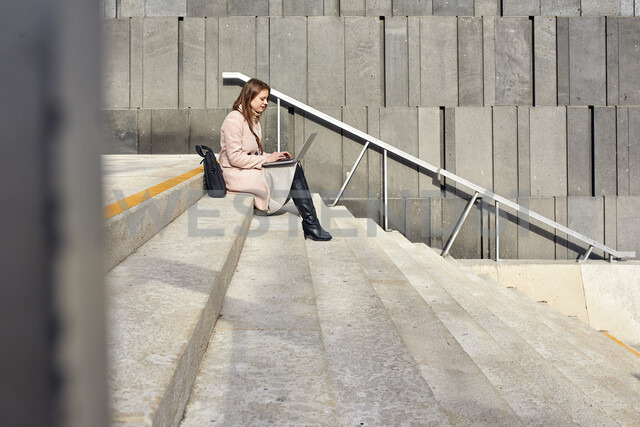 Austria, Vienna, young woman sitting on stairs at MuseumsQuartier using laptop - ZEDF01933 - Zeljko Dangubic/Westend61