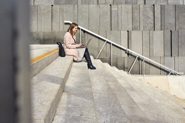 Austria, Vienna, young woman sitting on stairs at MuseumsQuartier using laptop - ZEDF01933